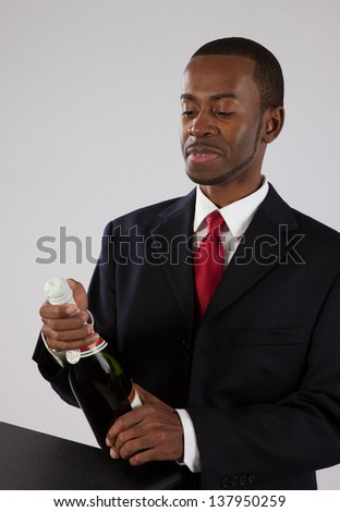 Handsome black man in a business suit, holding a bottle of wine with a happy expression as he looks at the bottle