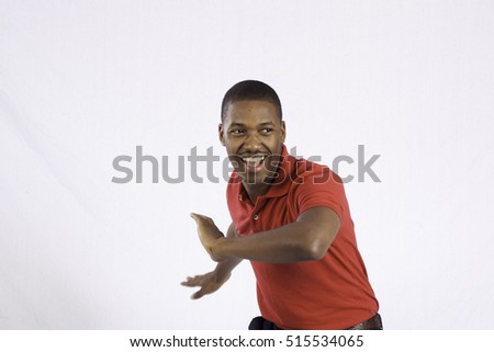 Handsome Black man in a red shirt, dancing for joy