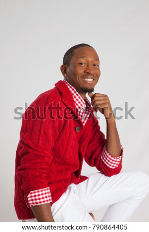Handsome Black man in a red sweater, smiling with his chin on his hand