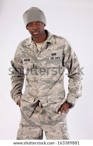 Handsome black man in a United States Air Force fatigues, looking at the camera with a thoughtful expression with his hands in his pockets - stock photo