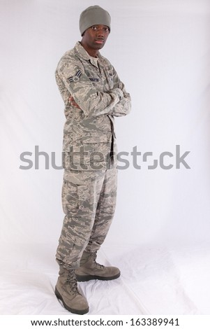 Handsome black man in a United States Air Force fatigues, looking at the camera with a thoughtful expression with his arms folded - stock photo