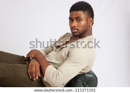Handsome Black man in shirt and slacks, reclining on a bench and looking thoughtful,