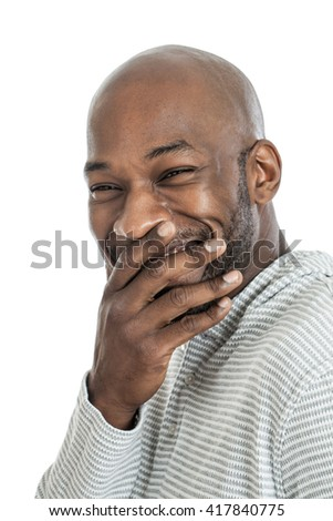 Handsome black man laughing covering mouth isolated on white background