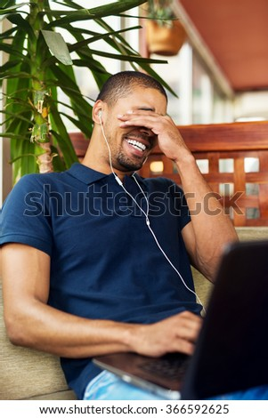 Handsome black man sitting at cafe bar,listening music and typing on laptop. Laughing. - stock photo