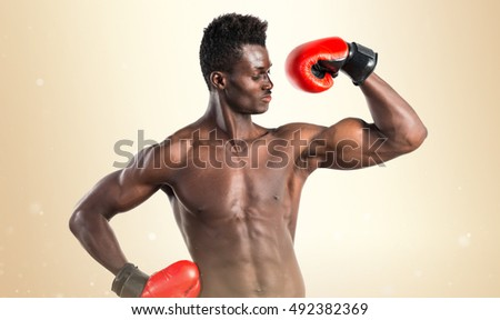 Handsome black man with boxing gloves over ocher background
