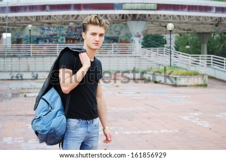 Handsome blond, blue eyed young man outdoors with ruck sack on shoulder, t-shirt and jeans - stock photo