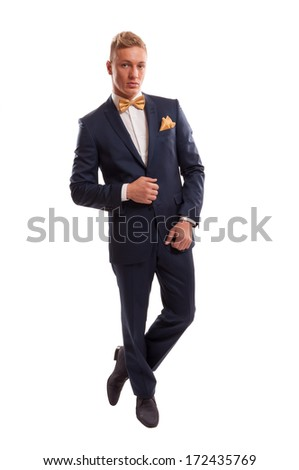 Handsome blond gentleman ready for a date wearing an elegant blue suit with a golden bow tie and a golden handkerchief