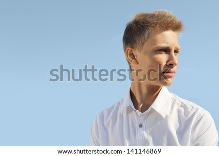 Handsome blond man on blue sky background at sunny day - stock photo