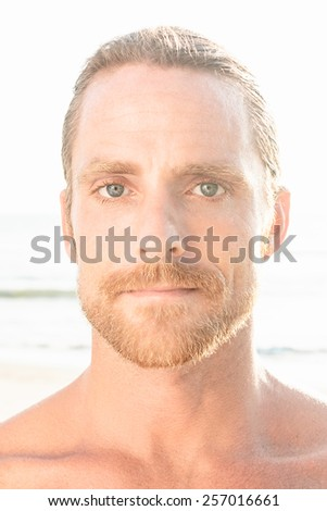 Handsome blond man with bare shoulders and a beard gazing directly at the camera on a high key beach background with flare from summer sunshine - stock photo