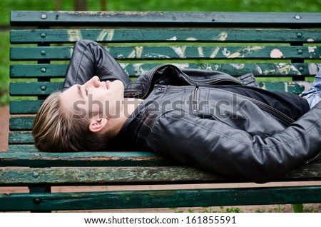 Handsome blond young man lying down on green, wooden park bench, looking up - stock photo