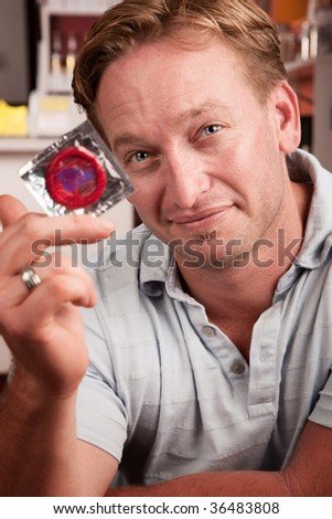Handsome blonde man holding a wrapped condom - stock photo