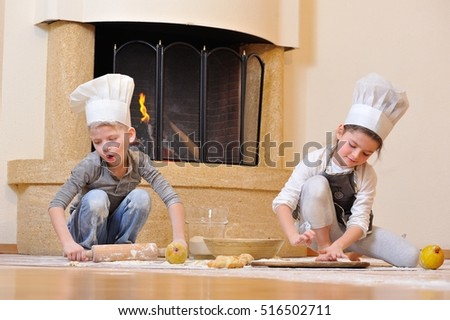 Handsome blue eyed kids in chef's hats near the fireplace: a boy sitting and playing cook with his pretty cousin, theyâ??re totally stained, sprinkle each other with flour and having fun