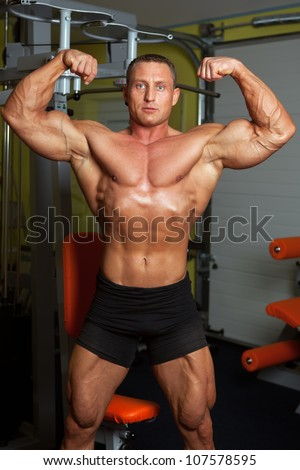 Handsome bodybuilder demonstrating pose in fitness club