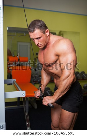Handsome bodybuilder exercise in fitness club - stock photo