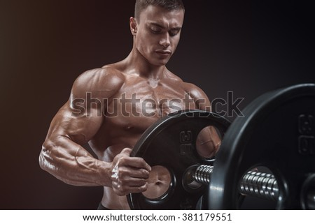 Handsome bodybuilder guy prepare to do exercises with barbell in a gym, keep barbell plate in hands - stock photo