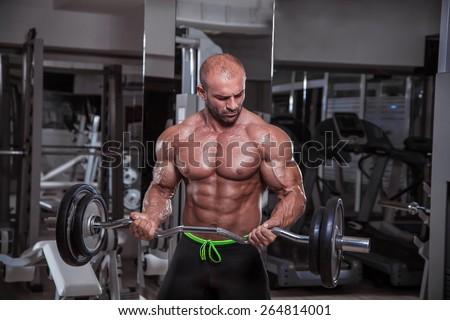 Handsome bodybuilder performing barbell biceps curls. - stock photo