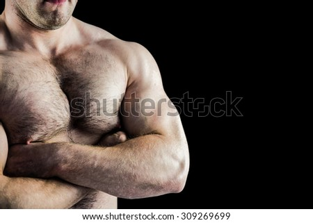 Handsome bodybuilder with arms crossed on black background