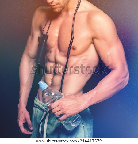 Handsome bodybuilder with water bottle and jump rope. Closeup of fit young man's abdomen and arms against dark background. Color filter applied.