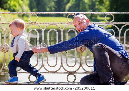 Handsome bold father on a bridge has caught by trousers his little son who is trying to run away - stock photo