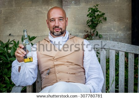 Handsome bold man dressed in regency period costume sitting on the bench with bottle of beer. Image with selective focus