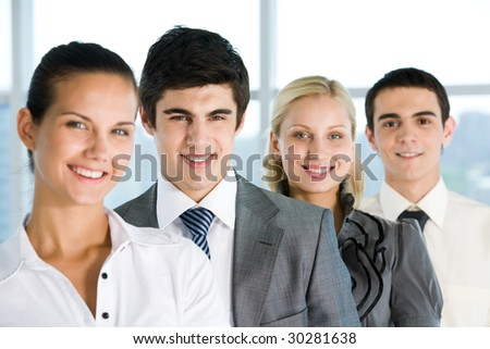 Handsome boss looking at camera with smile surrounded by employees