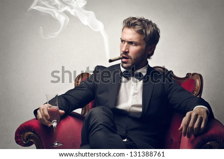 handsome boss sitting on the armchair smokes cigar - stock photo