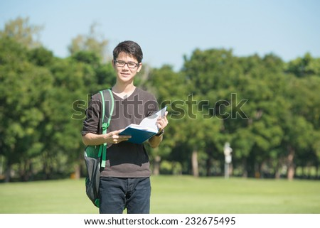 Handsome boy holding an open book, read background summer green park - stock photo