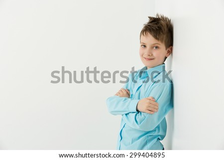 Handsome boy in blue shirt standing near wall over white background. Copy space.  - stock photo