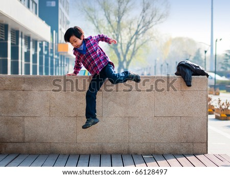 Handsome boy model jumping over wall