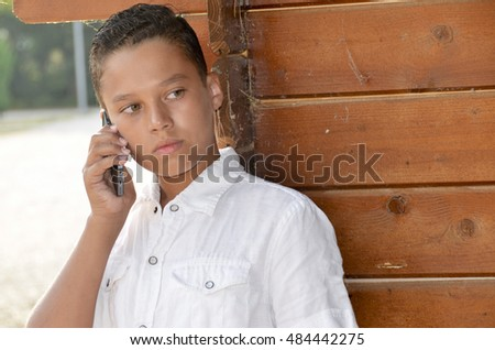 handsome boy on the phone leaning on an old cottage