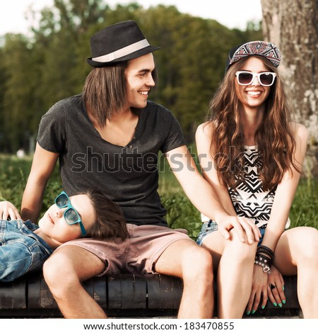 handsome boy puts hand on girl's knee while another girl  lies on his knee - stock photo