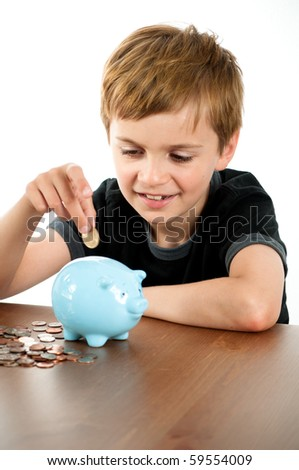 Handsome Boy Putting Money in Blue Piggy Bank - stock photo