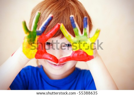 handsome boy shows his hands painted with paint - stock photo