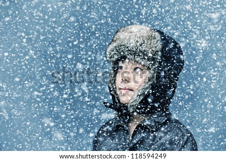 Handsome boy smiling and looking up in the snow - stock photo