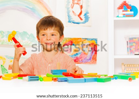 Handsome boy with toy hammer in the classroom