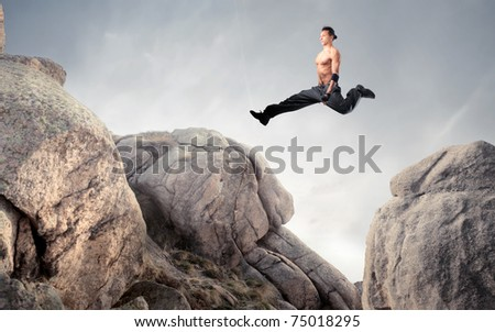 Handsome brawny man jumping from a rock to another