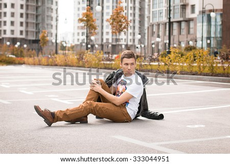 Handsome brown-haired young man in beige pants sitting on the ground. Autumn. - stock photo