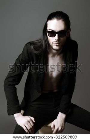 Handsome brunet man in black suit and sunglasses. Fashion studio shot. - stock photo
