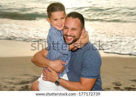 Handsome brunette father and son hugging at the beach at sunrise  - stock photo