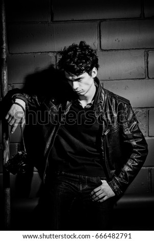 Handsome brunette male model in leather jacket with camera at dark wall with ladder