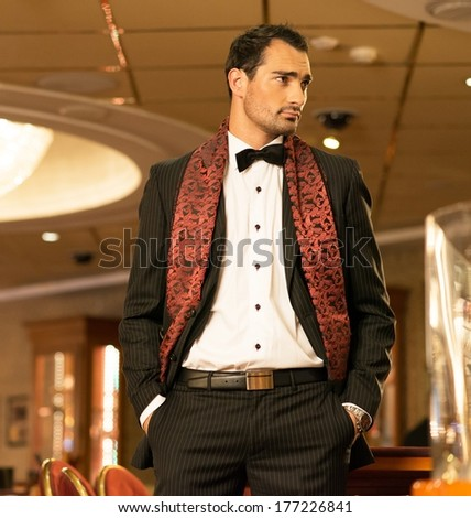 Handsome brunette wearing suit and scarf in luxury interior  - stock photo