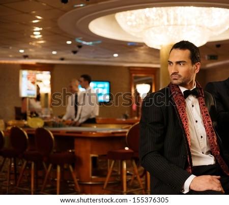 Handsome brunette wearing suit in luxury casino interior  - stock photo