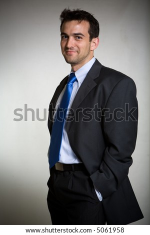 Handsome brunette young smiling business man wearing business suit with blue tie standing with hands in pockets
