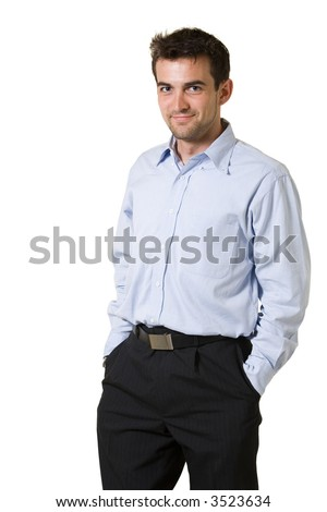 Handsome brunette young smiling man wearing blue dress shirt with hands in pockets standing on white background