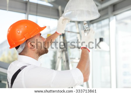 Handsome builder is screwing an electric light bulb into a fixture. He is standing and looking up with concentration - stock photo