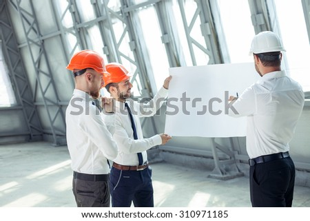 Handsome builders are holding a blueprint and looking at it seriously. They are discussing the plan of a new building. The engineer is pointing at paper with explanations. His colleague is smiling