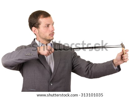 Handsome buisness man concentrated aiming a slingshot isolated over white background.
