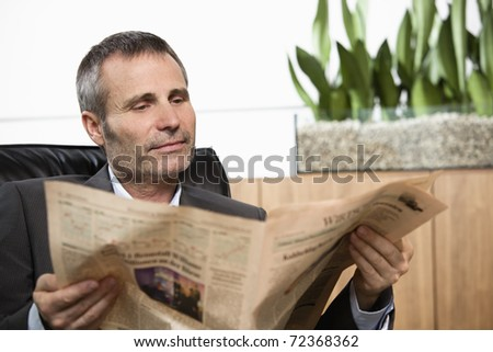 Handsome business executive sitting in office chair reading newspaper. - stock photo