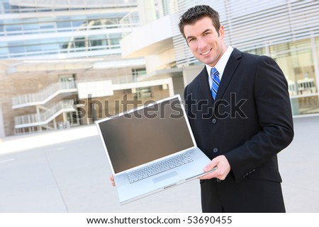 Handsome business man at office holding laptop computer - stock photo