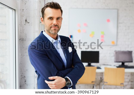Handsome business man at office looking at camera - stock photo